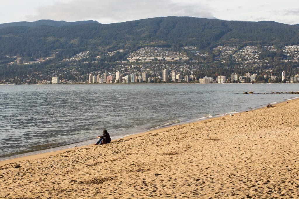 Frau am Third Beach im Hintergrund die Stadt