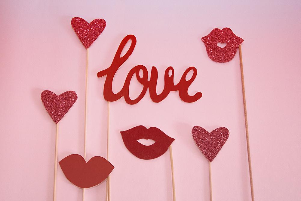 Schriftzug Love mit Herzchen und Kussmündern